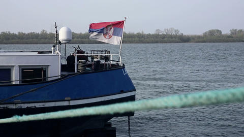 Ship on the river Danube anchored at the docks with Fluttering flag of Serbia. Slow motion 60fps Live Action