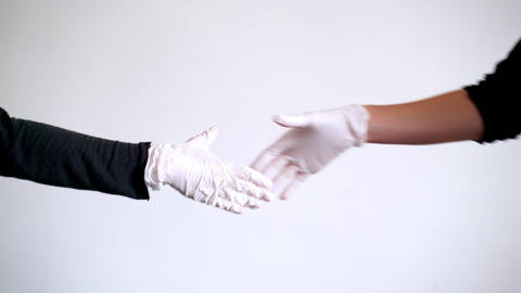 A man and a woman in latex gloves shake hands. Close-up of hands. Safe contact Live Action