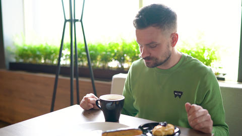 Bearded man with curled up mustache eats chocolate eclair and drinks coffee in Live Action