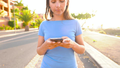 Woman in a blue dress using smartphone while walks on a palm street at sunset Live Action