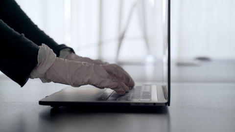 A woman works from home. Hands in latex gloves are typing on the laptop. Home Live Action
