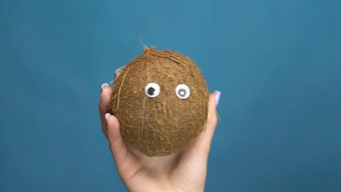 Coconut with eyes in a woman hand close-up. Coconut shakes and twists eyes on a Live Action