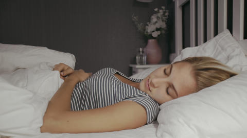 Young woman lying in the bed at night. Beautiful blond sleeping girl. Woman has Live Action