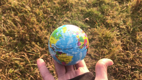 Female holding global earth in her hand, against yellow grass, ecology concept Live Action