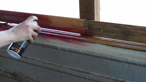 Paint in red painting a wooden wall in red video footage Live Action