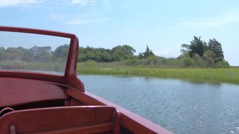 Wooden boat floating near coastal grasses Footage