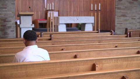 Man sits in an empty church praying Footage