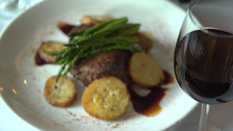 Left pan of a fillet mignon meal with red wine Footage