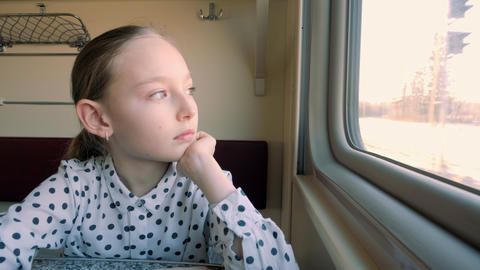 Daydreaming young girl looking at train window Live Action