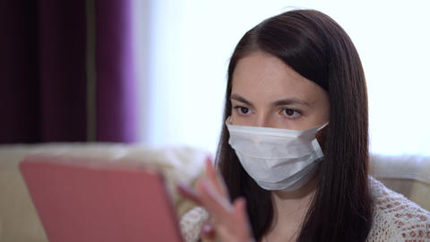 Woman in a Medical Mask Uses a Tablet at Home During Quarantine Live Action