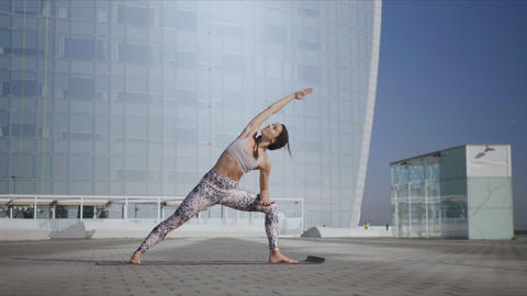 Girl performing yoga at street. Woman doing extended side angle pose at street Live Action