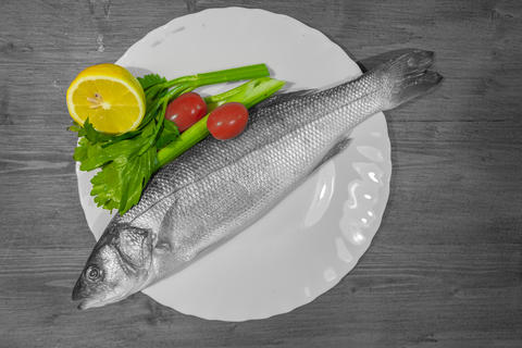 Color isolation effect of white dish with sea bass, lemon, celery and tomatoes Photo