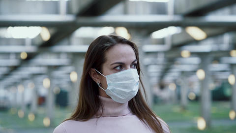 A girl in a protective medical mask on her face looks around Live Action