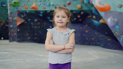 Portrait of beautiful little girl in indoor climbing facility standing alone Live Action