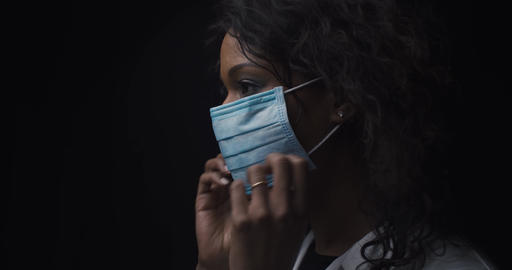 African woman puts on a medical mask Live Action