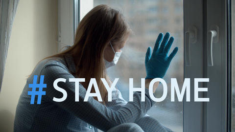 Hashtag stay home over woman looking out the window Live Action