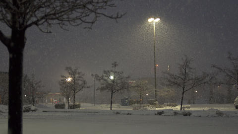 Heavy snow falling in empty parking lot during storm warning Live Action