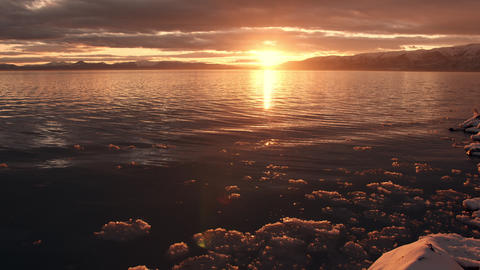 Ice floating on shoreline during golden sunset over lake Live Action