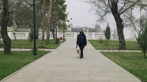 Back view of woman with black mask walks with her labrador dog in the park Live Action