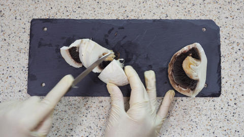 Cut raw portobello mushroom on chopping board with hygiene prevention gloves Live Action
