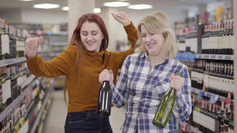 Happy adult Caucasian women dancing in wine shop with bottles of beverage in Live Action