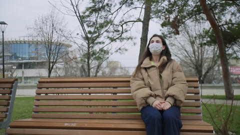 Beautiful woman with Medical Mask sits on bench in the park During Coronavirus Live Action