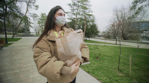 Young Woman Wearing Protective Mask stands with Shopping bag During Coronavirus Live Action
