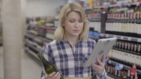 Young cheerful Caucasian woman comparing information in tablet with label on Live Action