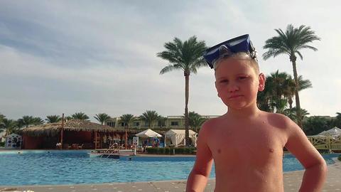Little wet boy stands near the pool Live Action