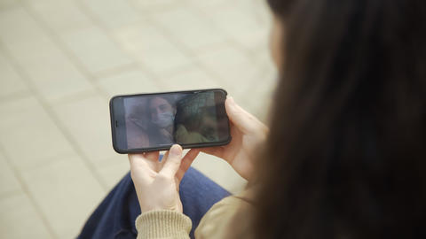 Young woman in protective mask watching video with herself smartphone in the Live Action