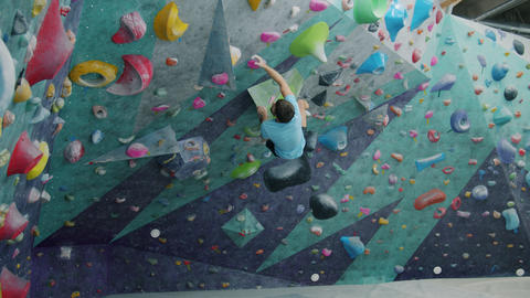 Slow motion of male climber climbing up wall then falling on safety impact pad Live Action