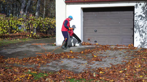 Male worker with leaf blower blowing leaves near garage Live Action