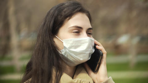 Side view of young woman outdoors with medical face mask for protection of virus Live Action