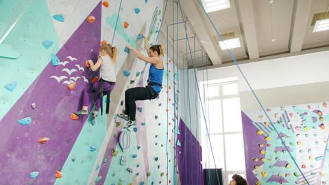 Kid and young lady climbing indoors in sports center being supported by Live Action