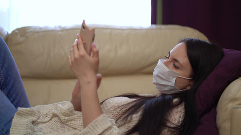 Woman in a Medical Mask Uses a Smartphone at Home During Quarantine Live Action