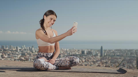 Sportsoman taking selfie on smartphone at city. Yoga woman sitting in lotus pose Live Action