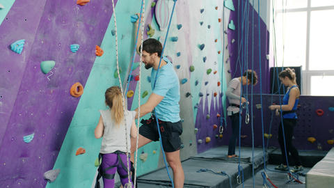 Male instructor talking to little girl in climbing gym explaining safety Live Action