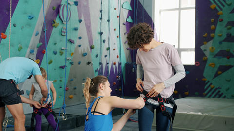 Instructors helping clients to put on safety harnesses in rock climbing center Acción en vivo