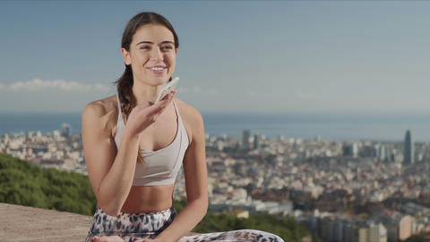 Smiling fit woman recording voice message on smartphone in city of Barcelona Live Action