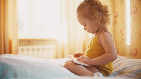 Focused baby girl looks at pictures in the little book in sunny room at home Acción en vivo