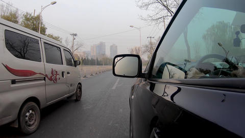 Side view of the car and driver inside the car on the road of Beijing Live Action