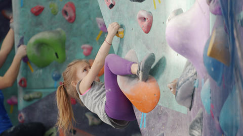 Serious kid concentrated on rock-climbing in indoor facility moving up wall Live Action