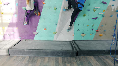 Tilt-up of woman and kid enjoying indoor rock-climbing in modern gym Live Action