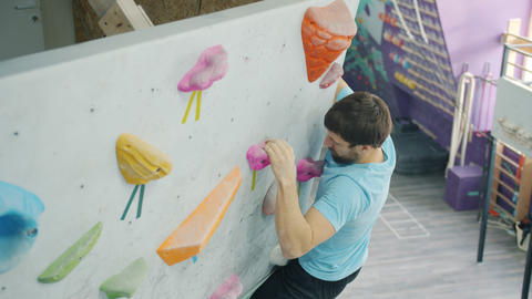 Experienced climber moving up artificial wall in gym grabbing rocks training Acción en vivo