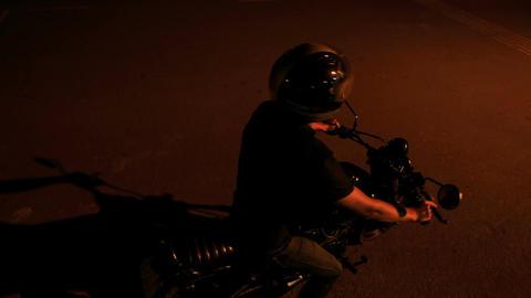 Guy in Helmet Mounts Motorcycle in Dark Street Live Action