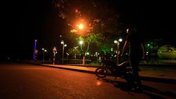 Guy in Helmet Mounts Motorcycle in Street Darkness Footage