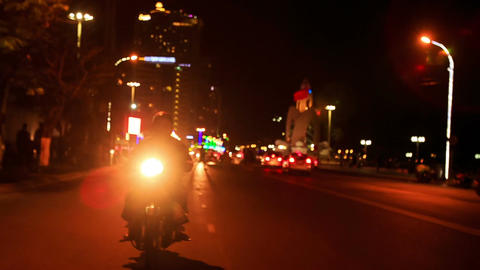Motorcycle Drives along Lit Street with Bright Head-light Footage