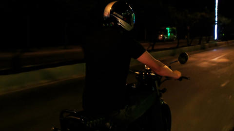 Guy Speeds on Motorcycle along Lit Street at Night Live Action