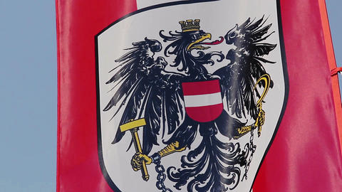 Austrian flag with coat of arms, national emblem waving in sky Footage
