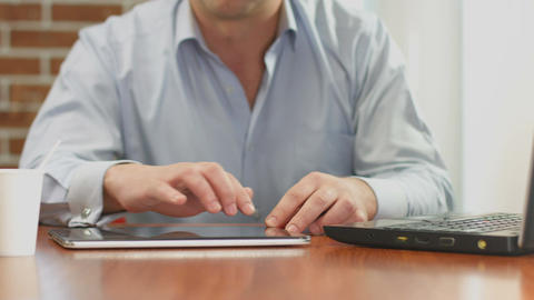 Man browsing internet pages on ipad, reading news feed online Live Action
